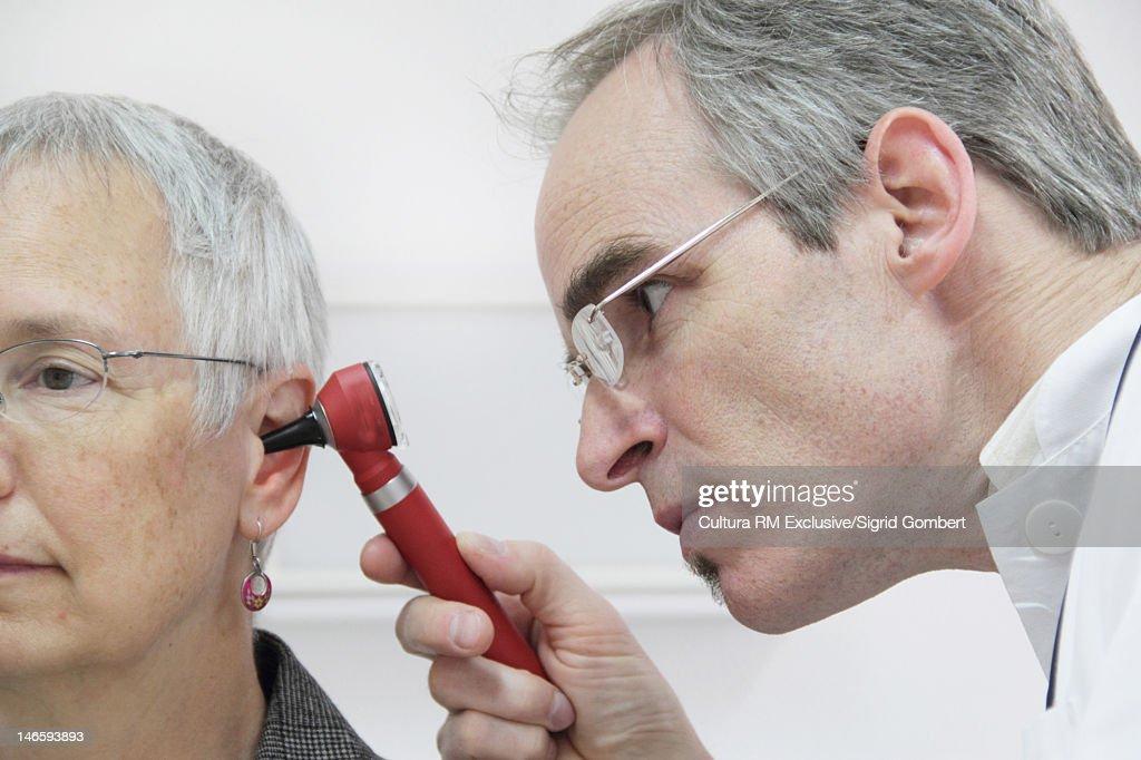 Doctor examining patients ear : Stock Photo