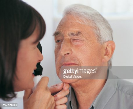 Doctor Examining Patient's Eye With a Occluder : Stock Photo