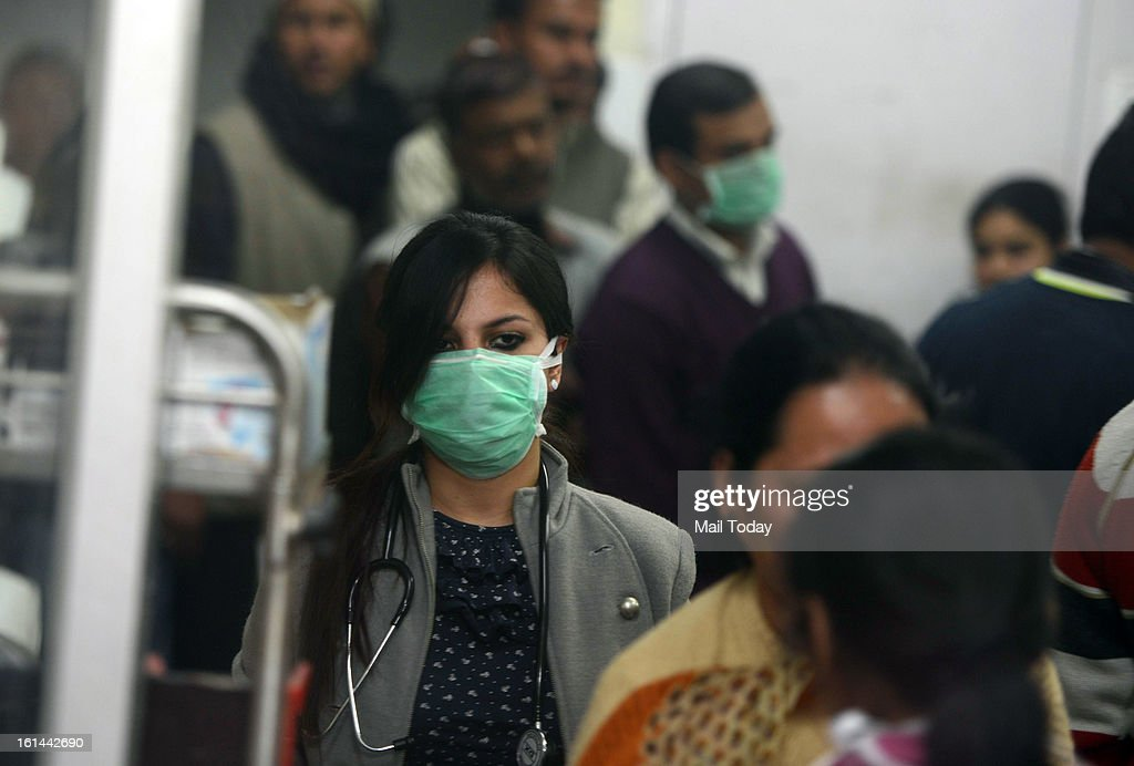 A doctor examining patients in the emergency ward of RML hospital with a face mask on as a precautionary measure from swine flu.