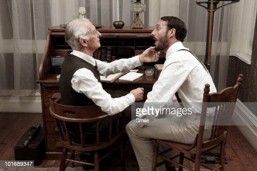 Doctor examining patient's mouth : Stock Photo