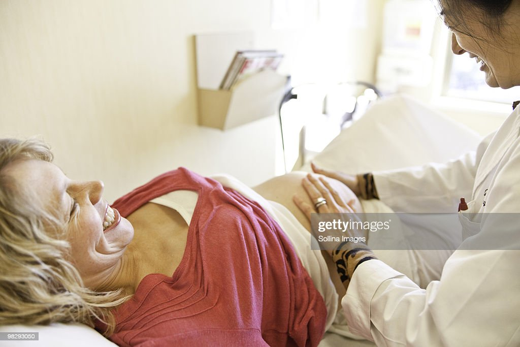 Doctor examining pregnant woman in exam room : Stock Photo