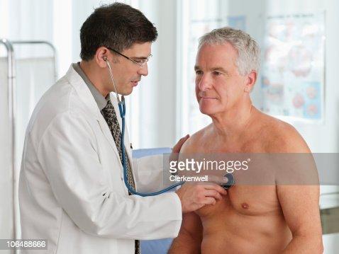 Doctor examining senior man with stethoscope : Stock Photo