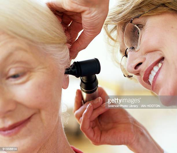 Doctor examining senior woman's ear