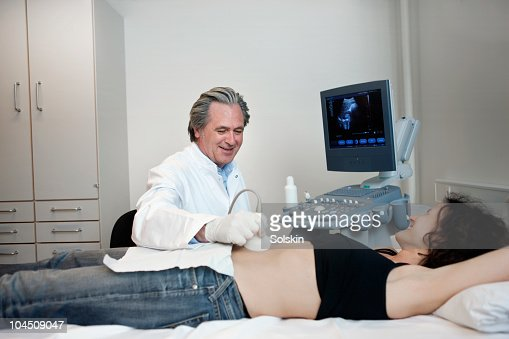 doctor examining woman with abdominal ultrasound : Stock Photo