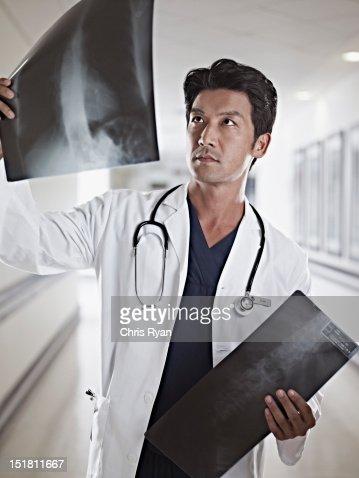 Doctor examining x-rays in hospital corridor : Stock Photo