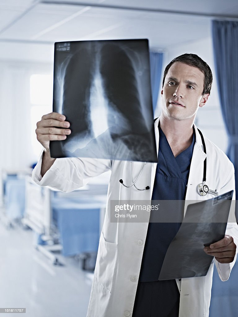 Doctor examining x-rays in hospital room