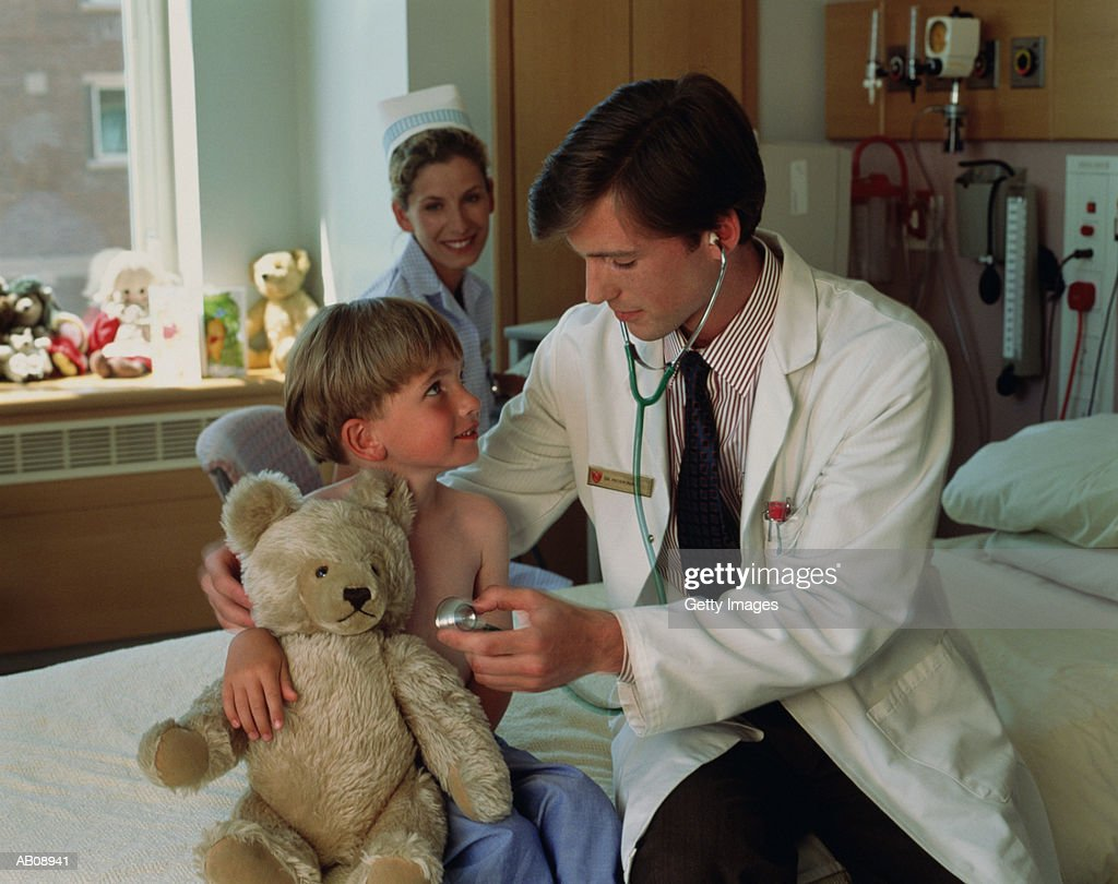 Doctor examining young patient on hospital bed : Stock Photo