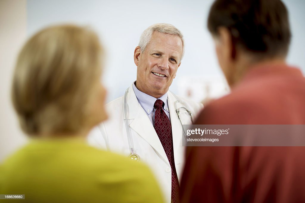 Doctor Explaining Medical Results To Couple. : Stock Photo