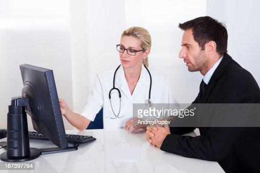 Doctor explaining something to a male patient : Bildbanksbilder