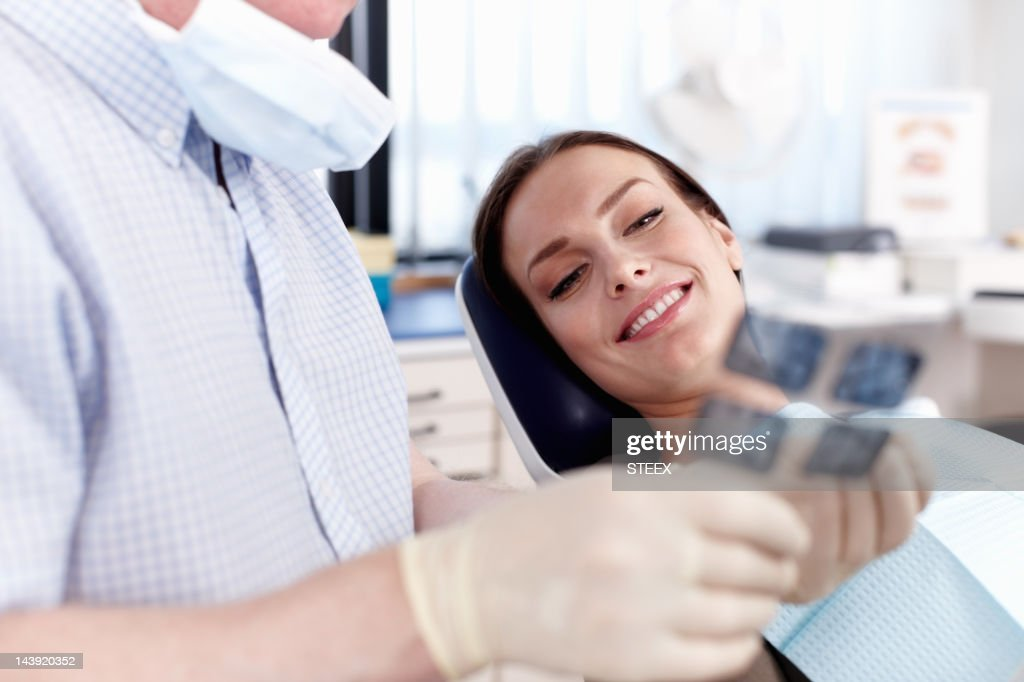 Doctor explaining x-ray to female patient : Stock Photo