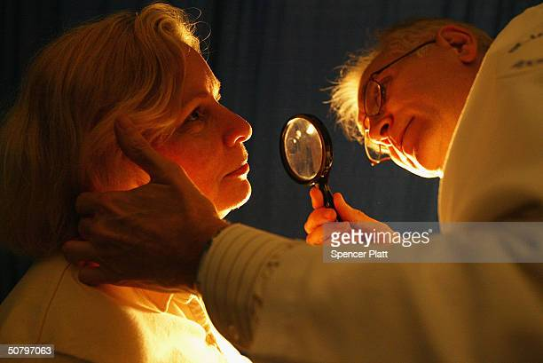 A doctor from the American Academy of Dermatology checks Christine Trerotoli for signs of skin cancer May 3 2004 at Bryant Park in New York City The...