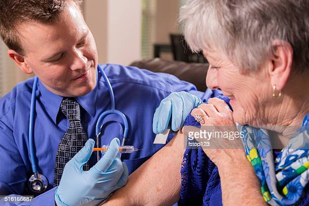 Doctor gives senior woman patient a vaccine.  Nursing home.