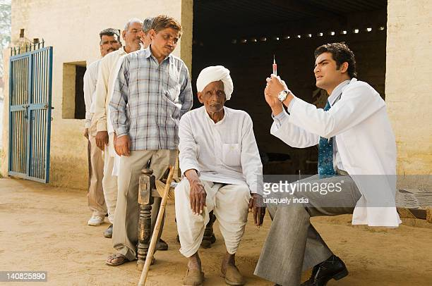 Doctor giving an injection to a farmer, Hasanpur, Haryana, India
