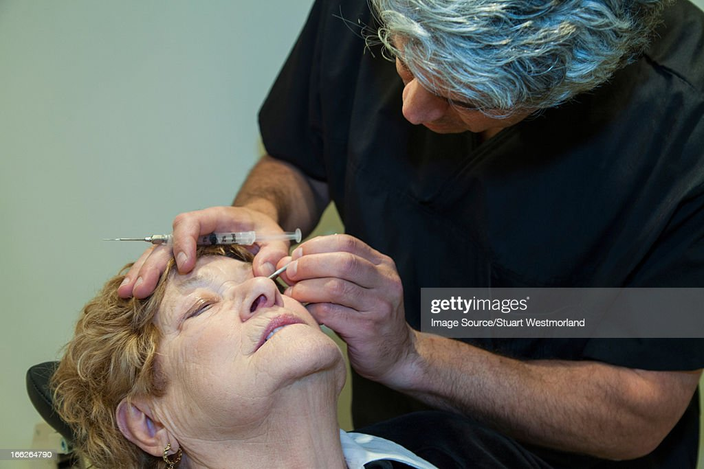 Doctor giving patient eye injection : Stock Photo