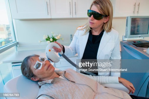 Doctor giving patient sunspot treatment : Stock Photo