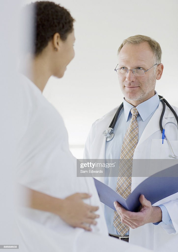 Doctor giving pregnant woman check-up : Stock Photo