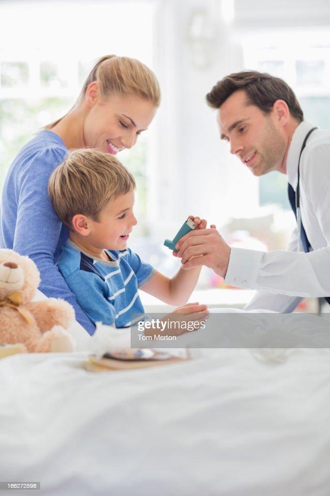 Doctor giving son asthma inhaler : Stock Photo