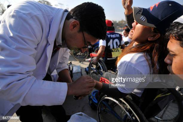 Doctor giving treatment to the injured Nepalese wheelchair racer after competing in the 1st Bodhisattvas In Action Wheelchair 4Km Marathon...