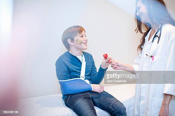 Doctor giving young boy a lollipop