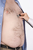 Doctor hand with stethoscope on overweight man's heart,, mid section