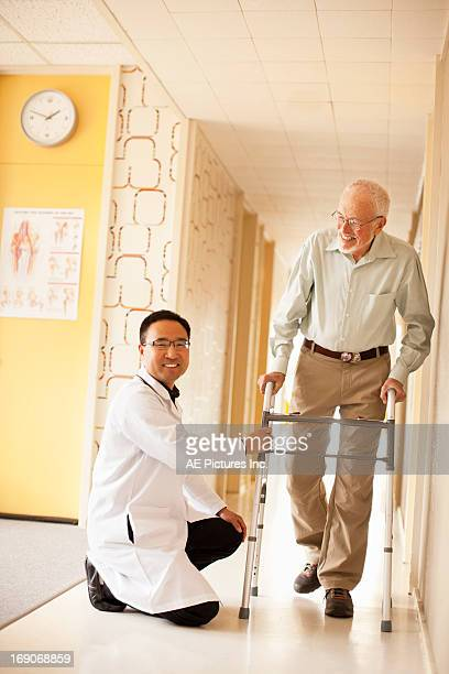 Doctor helps man with walking aid