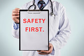 Doctor holding a clipboard with Safety first, Medical concept high quality and high resolution studio shoot
