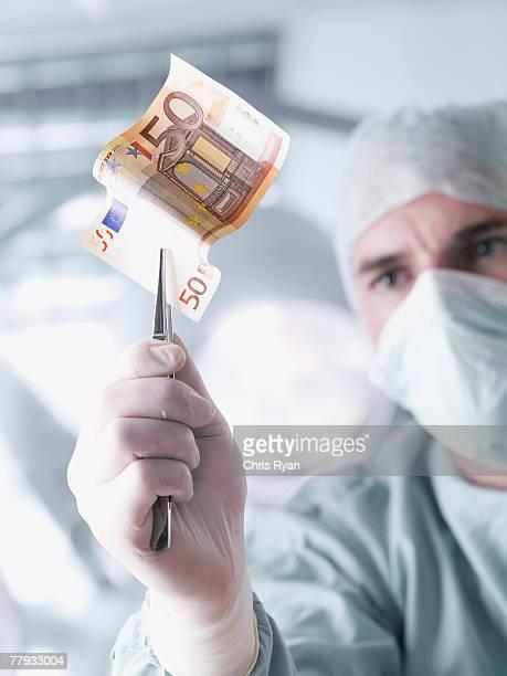 Arzt hält ein Fünfzigeuroschein mit Pinzette