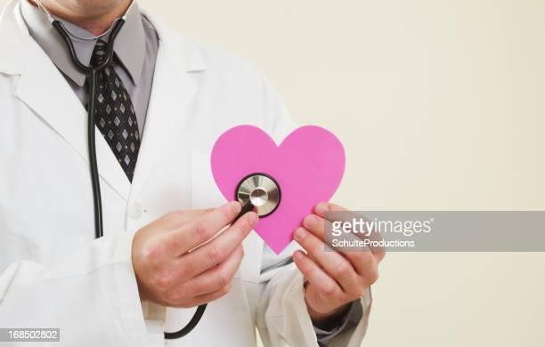 Doctor sosteniendo un corazón rosa