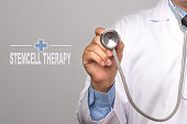 Doctor holding a stethoscope and word 'STEMCELL THERAPY' on gray background. Medical concept.