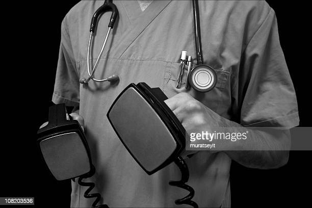 A doctor holding an electroshock in black and white