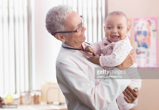 Doctor holding baby in office
