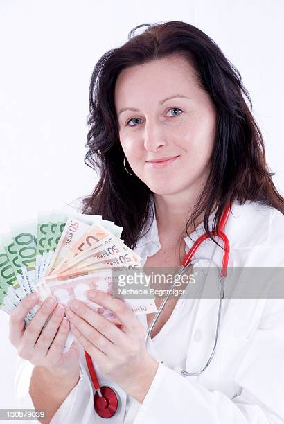 Doctor holding banknotes