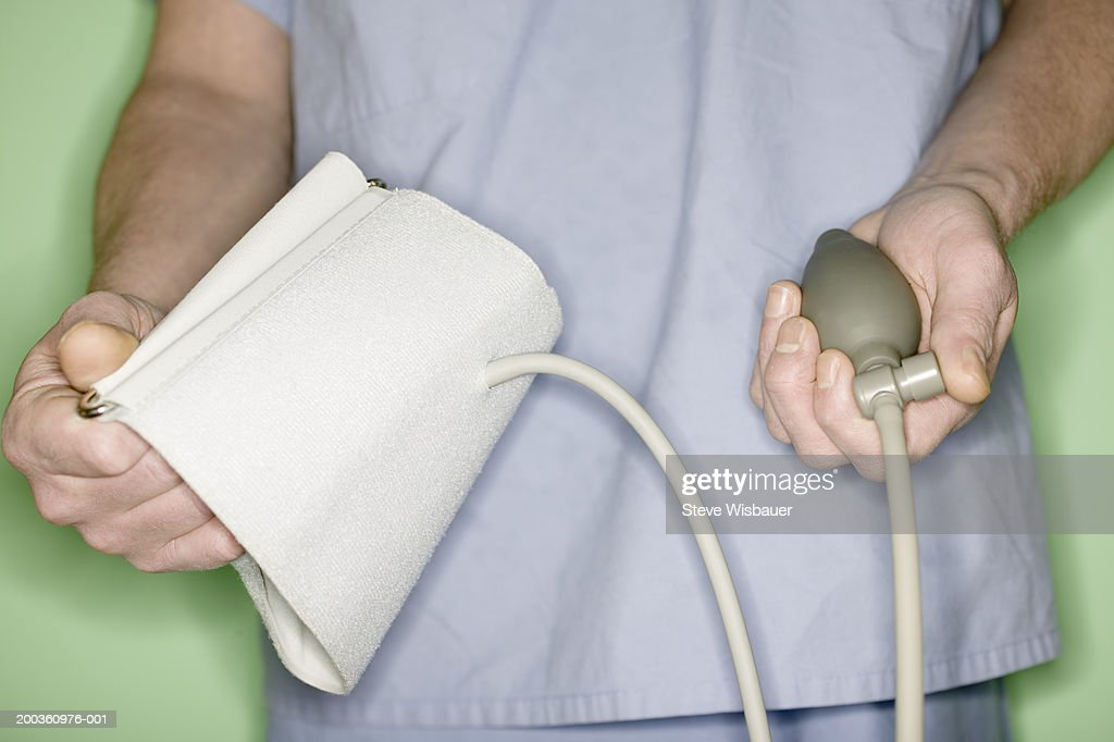 Doctor holding blood pressure gauge and cuff, mid section : Stock Photo