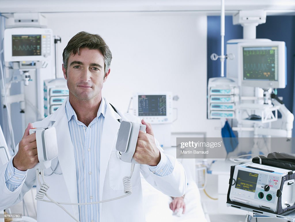 Doctor holding defibrillator paddles in hospital room : Stock Photo