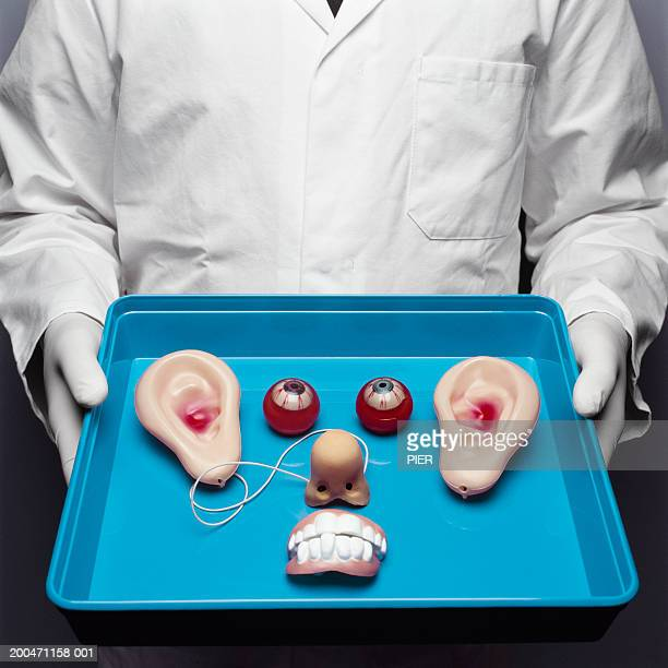 Doctor holding fake facial parts on tray, close-up