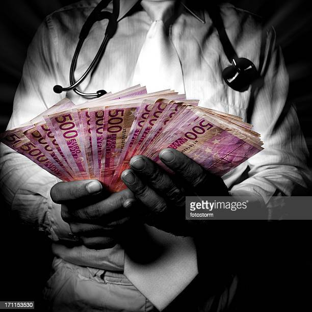 Doctor holding lot of money in his hands