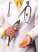 Doctor holding mackerel and Cod Liver oil tablets, close-up, mid section