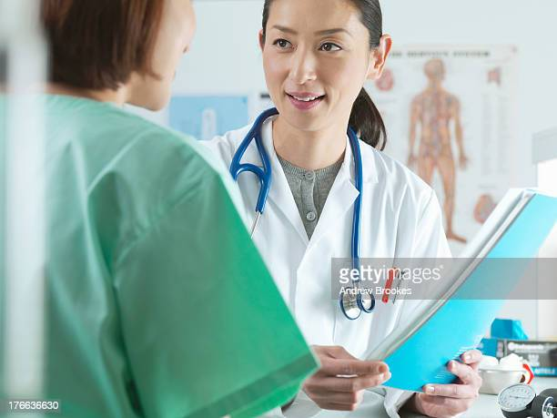 Doctor holding medical file with patient in examination room