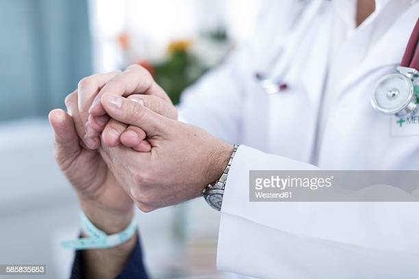 Doctor holding patients hand, close-up