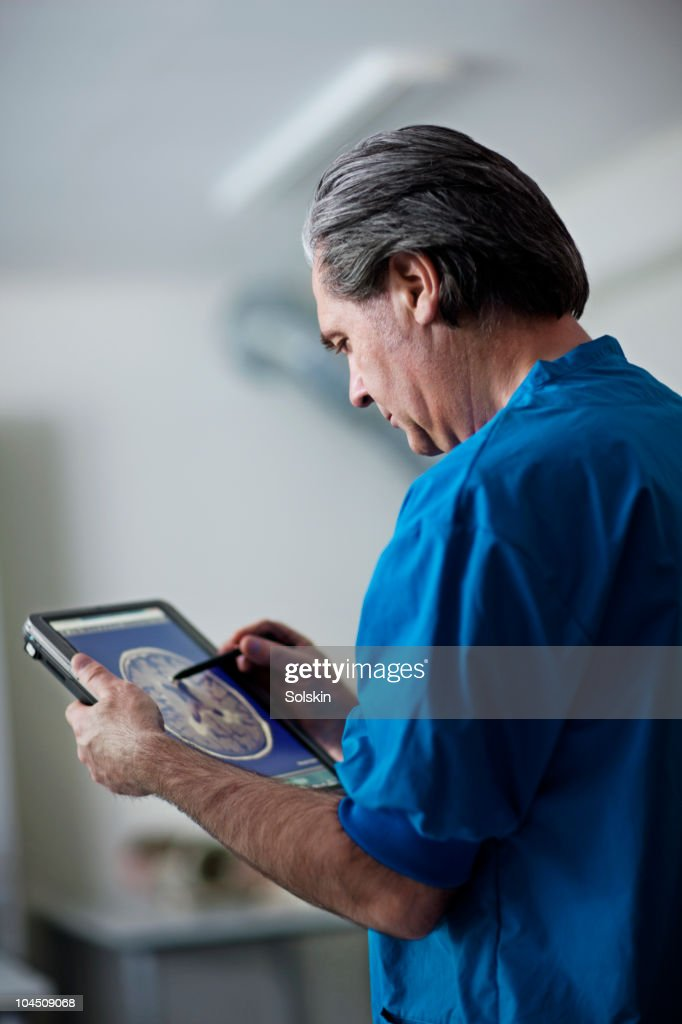 Doctor holding portable computer : Stock Photo