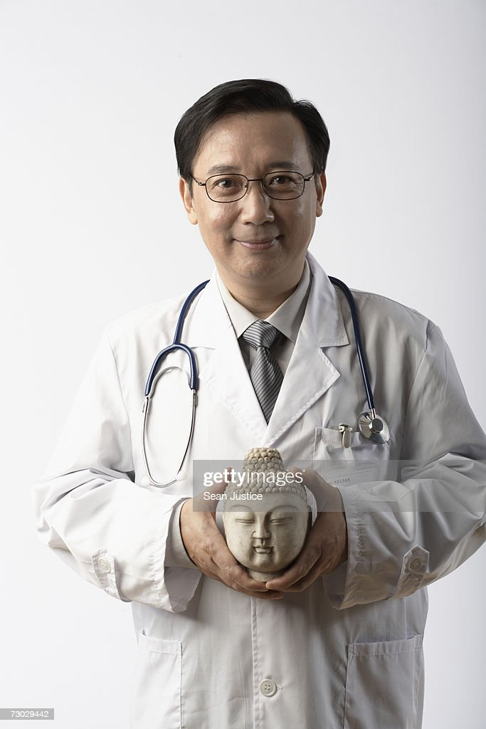 Doctor holding statue of Buddha, portrait : Stock Photo