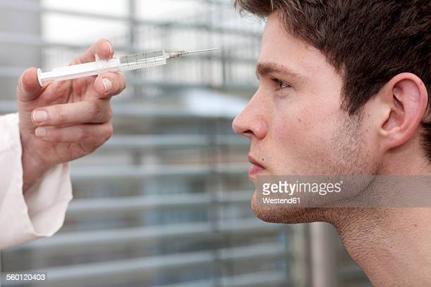 Doctor holding syringe at face of young man