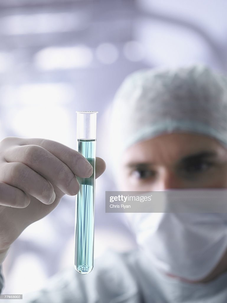 Doctor holding test tube in foreground : Stock Photo