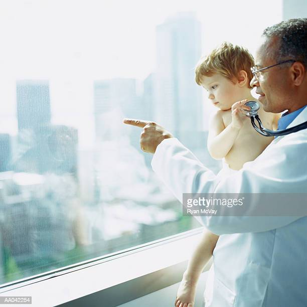 Doctor holding toddler boy (18-21 months), pointing out of window