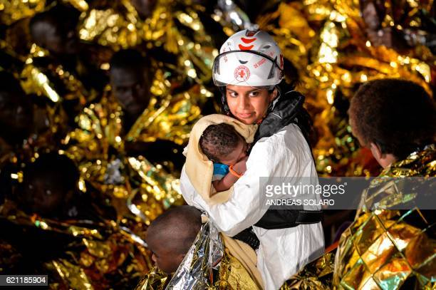 A doctor holds a baby during a rescue operation of migrants and refugees by the crew of the Topaz Responder a rescue ship run by Maltese NGO 'Moas'...