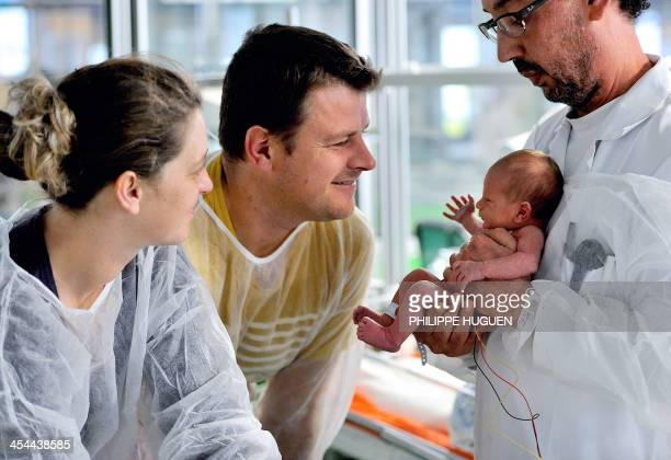 A doctor holds a premature baby as the baby's parents look on in the neonatal ward of the Centre Hospitalier de Lens in Lens northern France on...