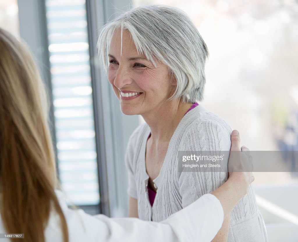 Doctor hugging smiling woman in office : Stock Photo