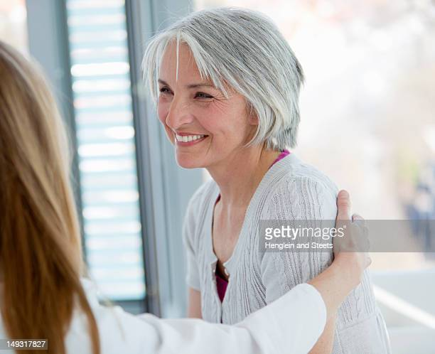 Doctor hugging smiling woman in office