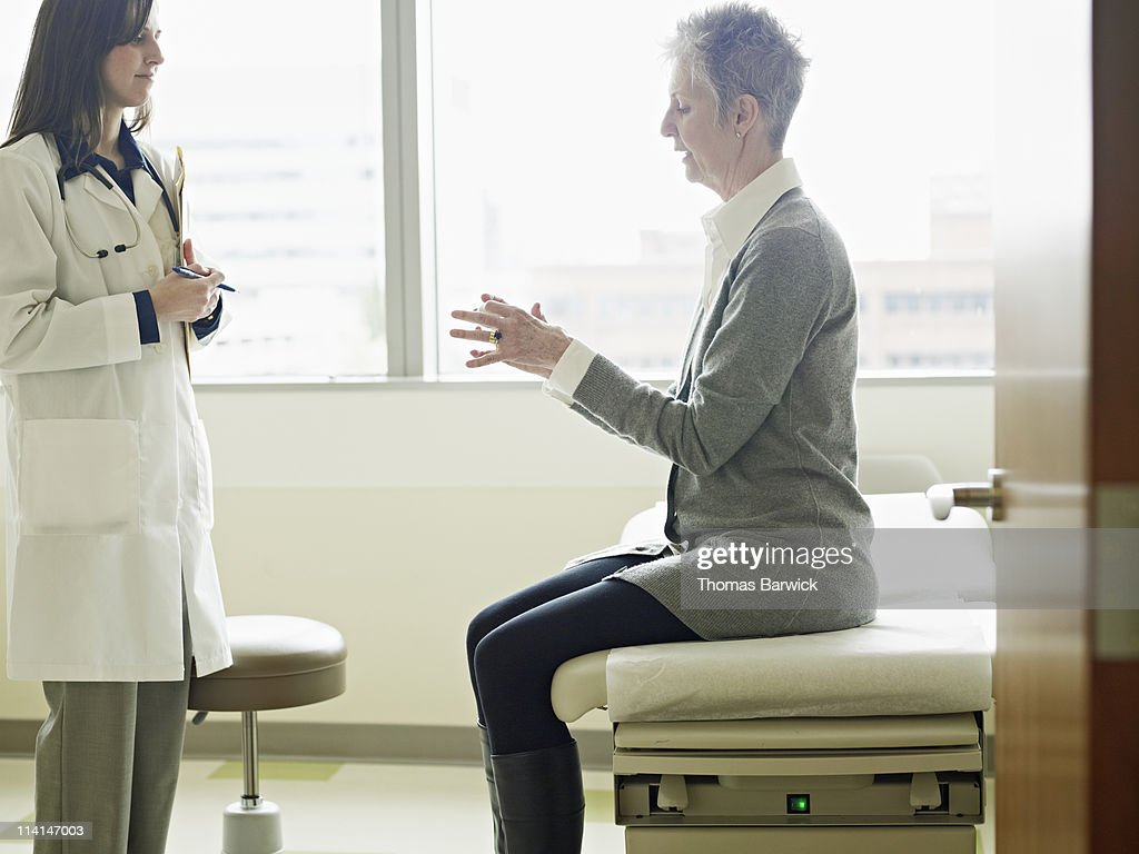 Doctor in discussion with patient in exam room : Stock Photo