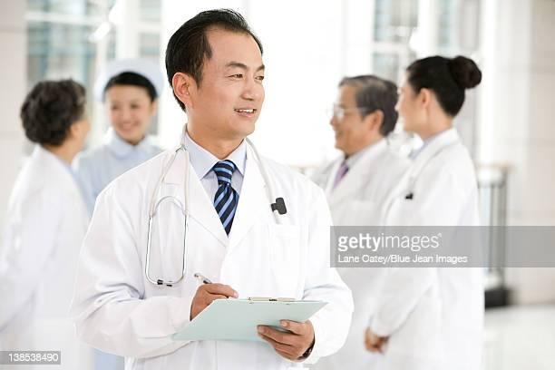 Doctor in Forground with Clipboard, Doctors and a Nurse in Background